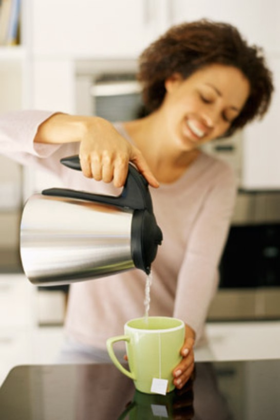 Woman pouring coffee and smiling in kitchen