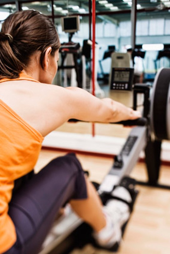 woman using rowing machine incorrectly