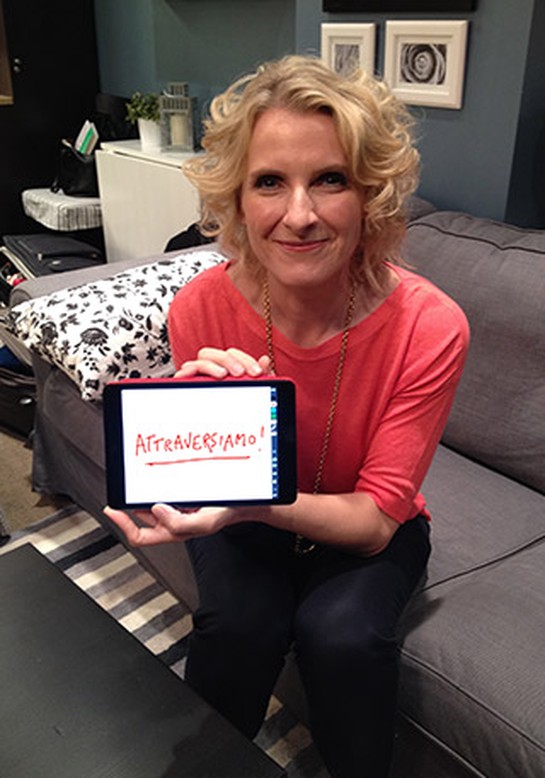 "Elizabeth Gilbert holding computer tablet that says, ""Attraversiamo!"""