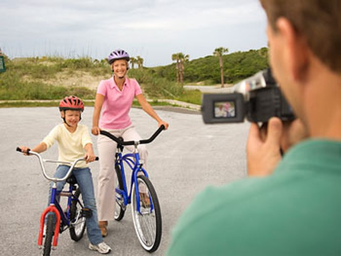 Dad filming mother and son riding their bikes