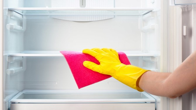 woman wiping down refrigerator