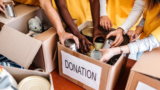 People placing canned goods into a donation box