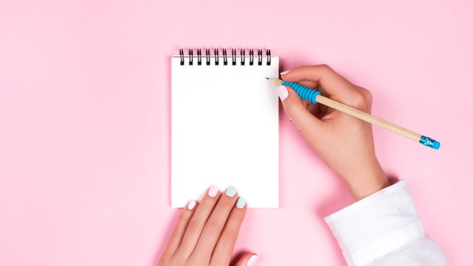 Woman holding pencil and spiral notepad
