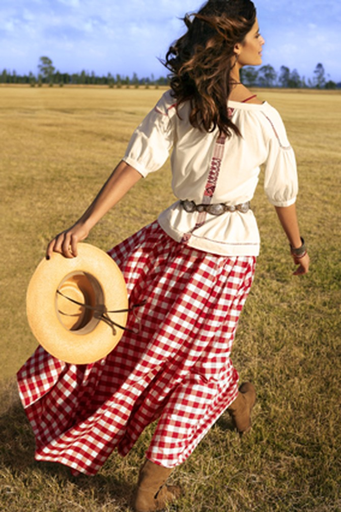Woman in a field in a gingham skirt