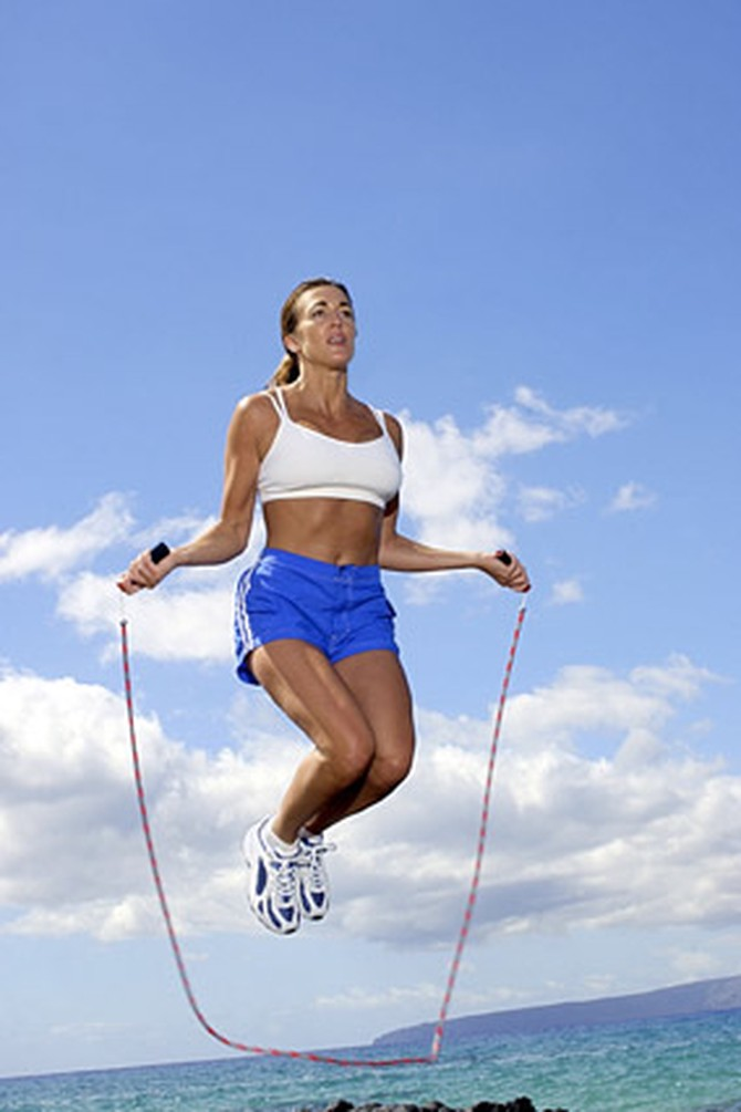 Woman jumping rope in sports bra and athletic shorts