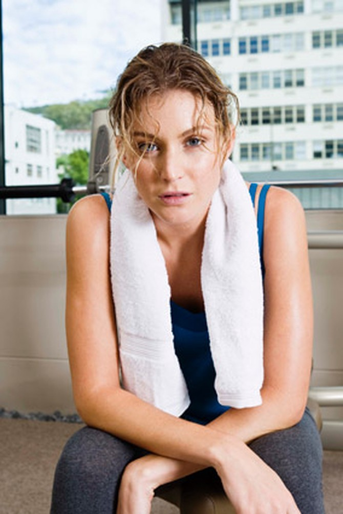 Sweaty woman with messy hair looking tired at the gym