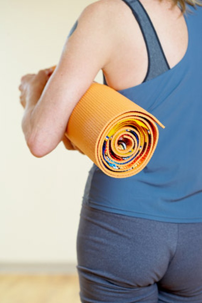 Woman walking with yoga mat