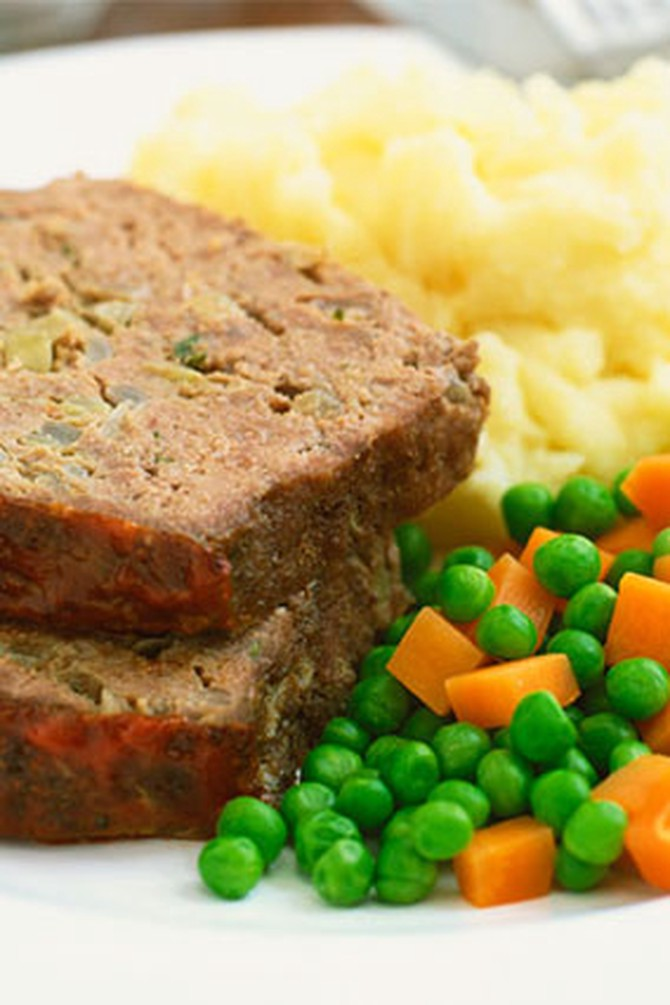 Slices of meatloaf on plate with peas and carrots and mashed potatoes