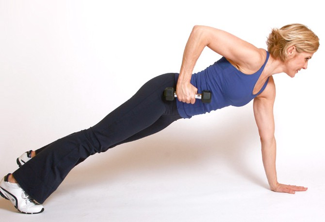Andrea Metcalf demonstrates the plank row and reach.