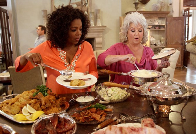 Oprah Winfrey and Paula Deen serving themselves food from a buffet