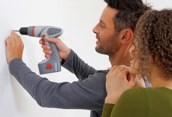 Woman watching man use power drill