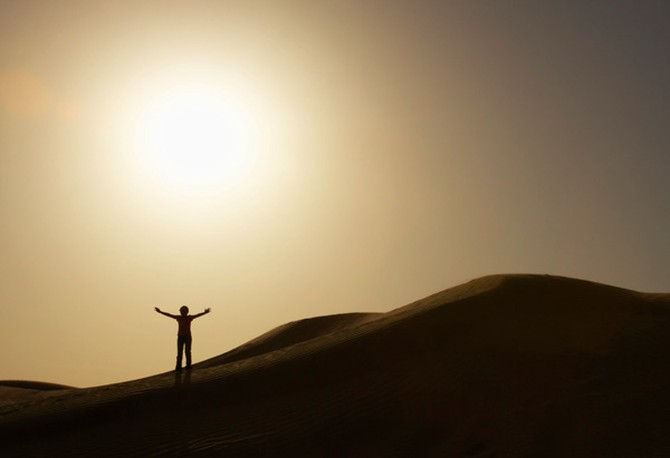 Person standing in desert shadow