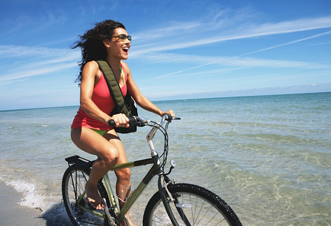 Woman riding bike on ocean shore