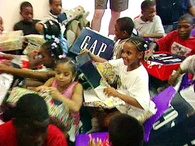 Kids at the Northern home unwrap their gifts from Gap.