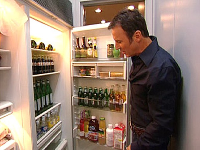 Colin Cowie checks his refrigerator for beverages.