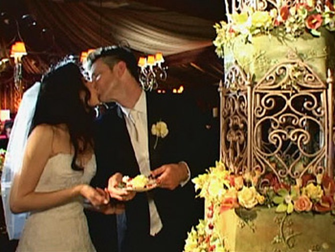 Bob and Urania kiss near the cake.