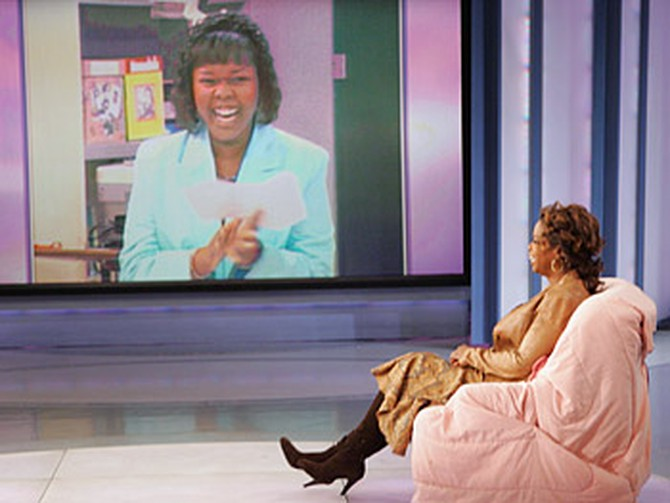 Oprah finally takes a seat in the chair Mrs. Adeniyi reserved for her.