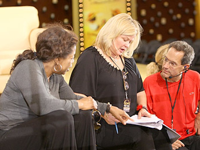 Oprah consults with an executive producer and stage manager.