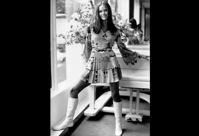 Ali MacGraw wearing a dress with white boots