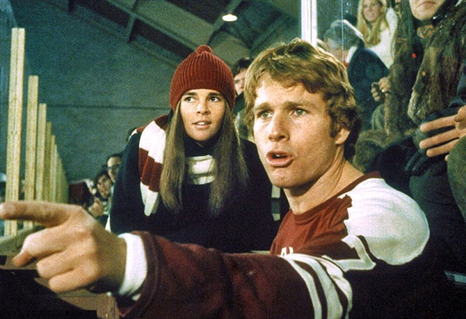 Ali MacGraw wearing a maroon hat and striped scarf in Love Story with Ryan O'Neal